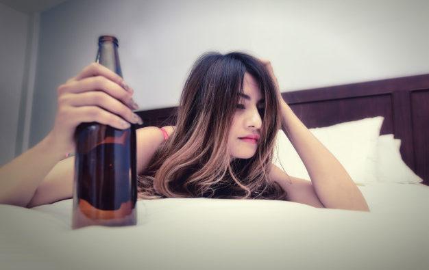 betrunkene-frau-auf-dem-bett-mit-flasche-in-der-hand